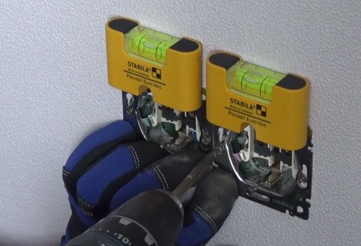 проверка горизонтальности установки розеток компактным уровнем электрика
