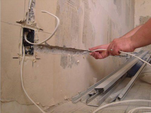 Штробы в бетонной стене, прорезанные болгаркой диском по бетону и обработанные перфоратором с зубилом. Так же на фото показано крепление проводов на пластиковые хомуты с дюбелями.