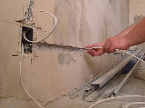 Штробление для укладки нового провода при выполнении работ по переносу розетки